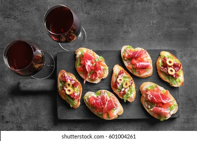 Tasty bruschetta served with wine on gray  background