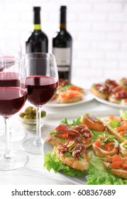 Tasty bruschetta served with wine on light background