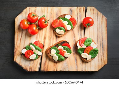 Tasty bruschettas with cherry tomatoes and mozzarella on wooden board