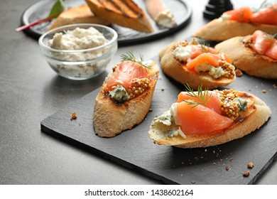 Tasty bruschettas with salmon and blue cheese served on table. Space for text