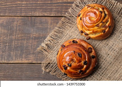 Tasty buns with raisins on a brown wooden table. fresh bakery. breakfast. bread. top view