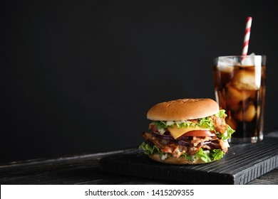 Tasty burger with bacon and cola on black background. Space for text