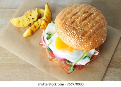 Tasty burger with bacon and egg on table