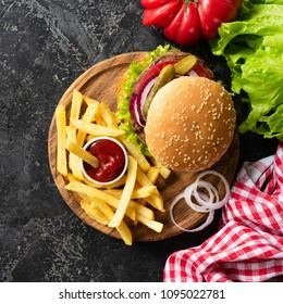 Tasty burger with beef, french fries and ketchup on dark background. Burger top view. Fast food fries and cheeseburger. Square crop