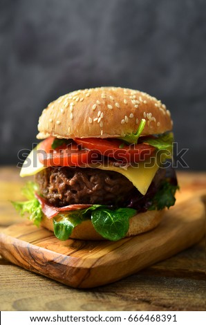 Tasty burger with cheese and vegetables on wooden table