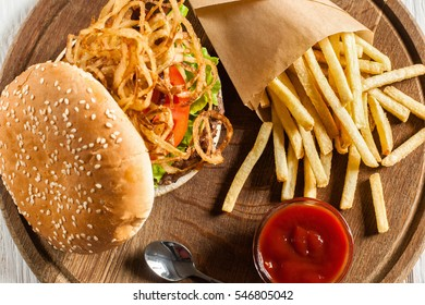 Tasty burger with french fries and ketchup flat lay. Top view on catering platter with hamburger and fried potato. Traditional american cuisine, fast and junk food, fat dining concept