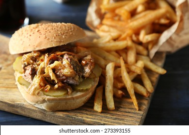 Tasty burger and french fries on plate, on wooden table background. Unhealthy food concept