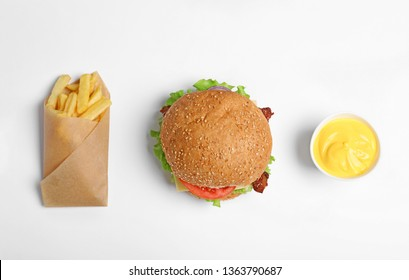 Tasty burger, french fries and sauce on white background, top view