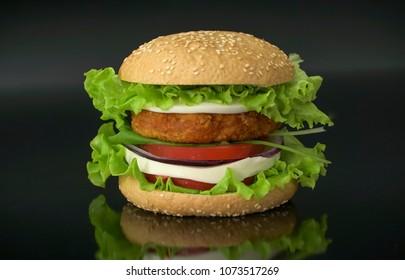 Tasty burger on black background. Homemade hamburger with fresh vegetables.