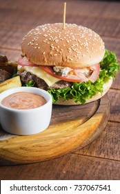 Tasty burger with potatoes and sauce on wooden board.