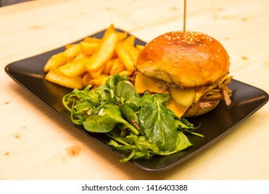 Tasty burger with salad and french fries on bistro or pub wooden table - Shutterstock ID 1416403388