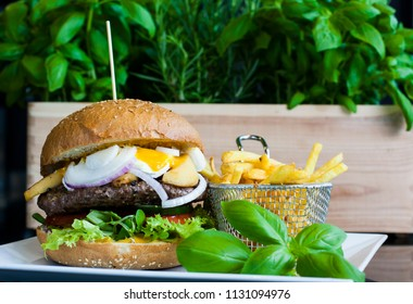 Tasty burgers with fried eggs and basket of French fries