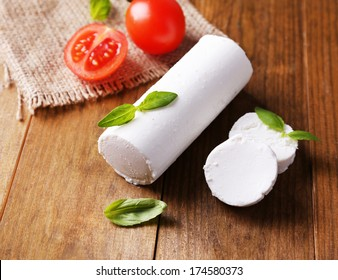 Tasty bushe cheese with basil and tomato, on wooden table