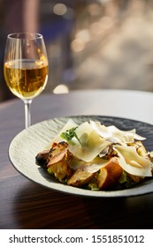 tasty Caesar salad with Parmesan slices served on plate with white wine in sunlight
