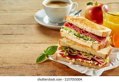 Tasty cafeteria breakfast with assorted toasted meat sandwiches, freshly squeezed orange juice, apple and cup of coffee on a rustic wood table with copy space