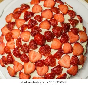 Tasty cake covered in strawberries.