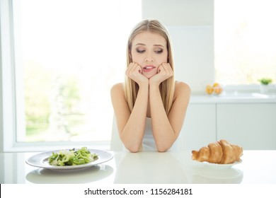Tasty cake vs beautiful fit figure shape person people concept. Close up photo portrait of pretty confused nervous minded puzzled lady wants to eat cookies sitting at table in white light room