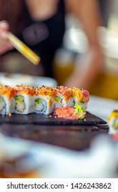 Tasty california roll, woman using chopsticks, eats delicious healthy sushi, enjoying oriental food, having lunch in a sushi bar, an asian restaurant menu