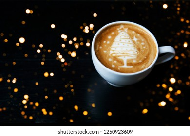 Tasty cappuccino with Christmas tree latte art with some blurred lights. Holiday concept.
