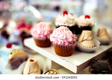Tasty caramel cupcakes with pink cream on top