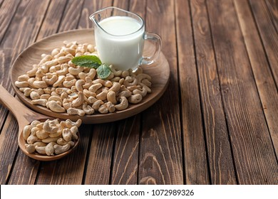 Tasty cashew nuts and jug of milk on wooden plate