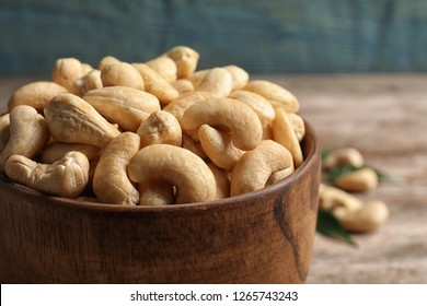 Tasty cashew nuts in wooden bowl on table, closeup