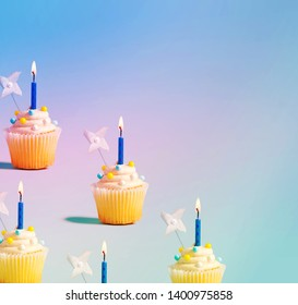 Tasty celebratory cupcakes with decorative lit candles