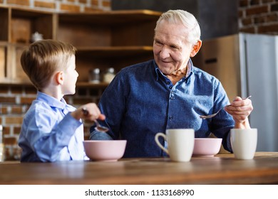 So tasty. Cheerful little boy and grandfather having a healthy breakfast while sitting in the kitchen