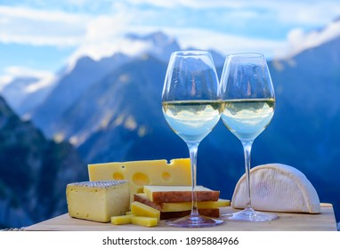Tasty cheese and wine from Savoy region in France, beaufort, emmental, tomme and reblochon de savoie cheeses and glass of white wine served outdoor in summer with Alpine mountains peaks on background