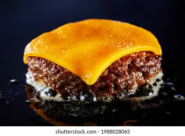 Tasty cheeseburger with beef patty sizzling on a grill in a close up on the melted cheese and juicy meat over a dark background for menu advertising