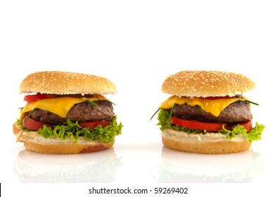 Tasty cheeseburgers with vegetables and bread rolls