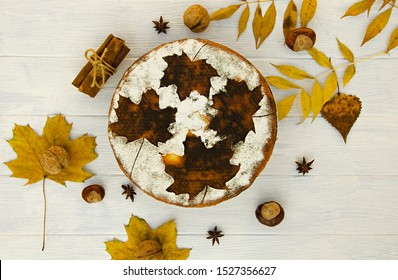Tasty cheesecake with pumpkin and autumn leaves on a light wooden table. Top view. Flat lay. Banner.