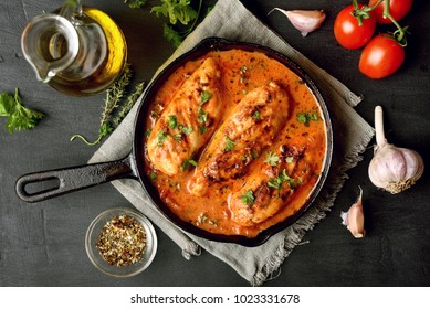 Tasty chicken breast with tomato sauce in frying pan over black background. Top view, flat lay