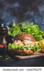 Tasty Chicken Burger With Cheese, Sauce, Lettuce On Wooden Serving Board. Closeup view, Selective focus