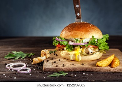 Tasty chicken hamburger on dark wooden board pierced with knife, surrounded by french fries, arugula and black pepper. Free space for text.