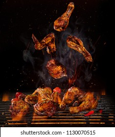 Tasty chicken legs and wings on the grill with fire flames