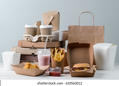 Tasty chicken Nuggets, milkshake, sauce, hamburger, French fries, hot chocolate and latte. Pizza boxes and paper bag, light wooden surface. Emotional eating.