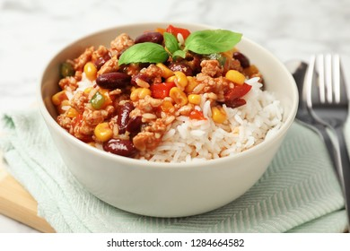 Tasty chili con carne served with rice in bowl on table