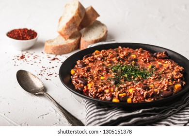 Tasty Chili con carne stew with fresh herbs on white
