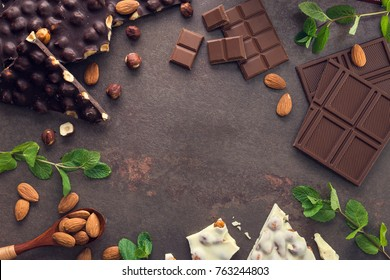 tasty chocolate bars with nuts, fresh mint and almond on a stone background. Sweet food