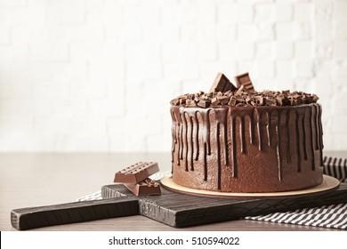 Tasty chocolate cake on brick wall background