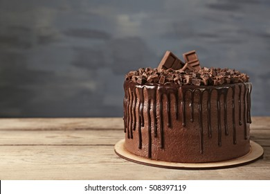 Tasty chocolate cake on grey wall background