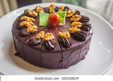 Tasty Chocolate Cake Topped with Strawberry and Walnuts Isolated on White Plate. Whole Chocolate Cake served at Wedding Party or Birthday Celebration Day time. Dark Chocolate Background with Copyspace