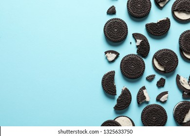 Tasty chocolate cookies with cream on color background, flat lay. Space for text