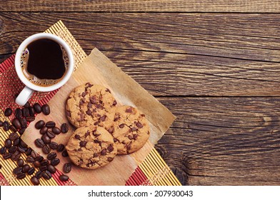 Tasty chocolate cookies and cup of coffee on wooden background. Top view