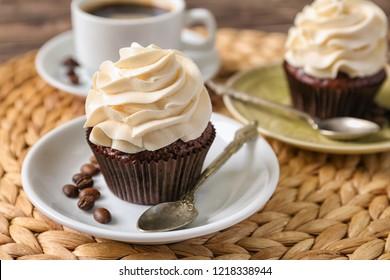 Tasty chocolate cupcake on wicker mat