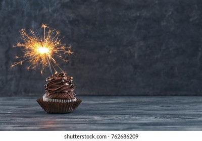 Tasty chocolate cupcake with sparkler on wooden table