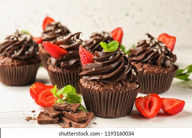 Tasty chocolate cupcakes with strawberry on white wooden table