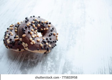 Tasty chocolate donuts on the grey wooden backround.