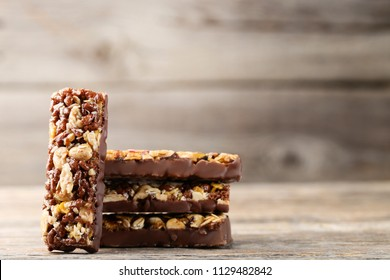 Tasty chocolate granola bars on wooden table